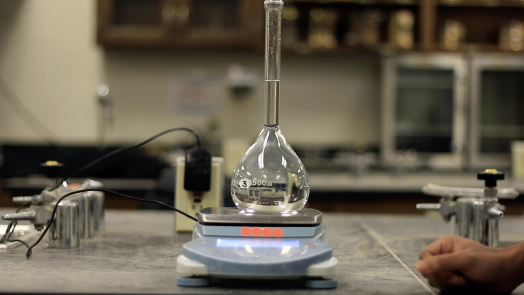 A round bottom glass flask in placed upon a weight scale to measure the weight. The glass flask is filled with water.