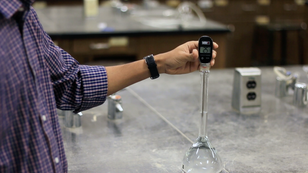 A person is standing on the left side of the image. He is holding a black colored thermometer. The stick of the thermometer is placed into a glass flask to measure the temperature of water. Thermometer shows 25 degrees Celsius.