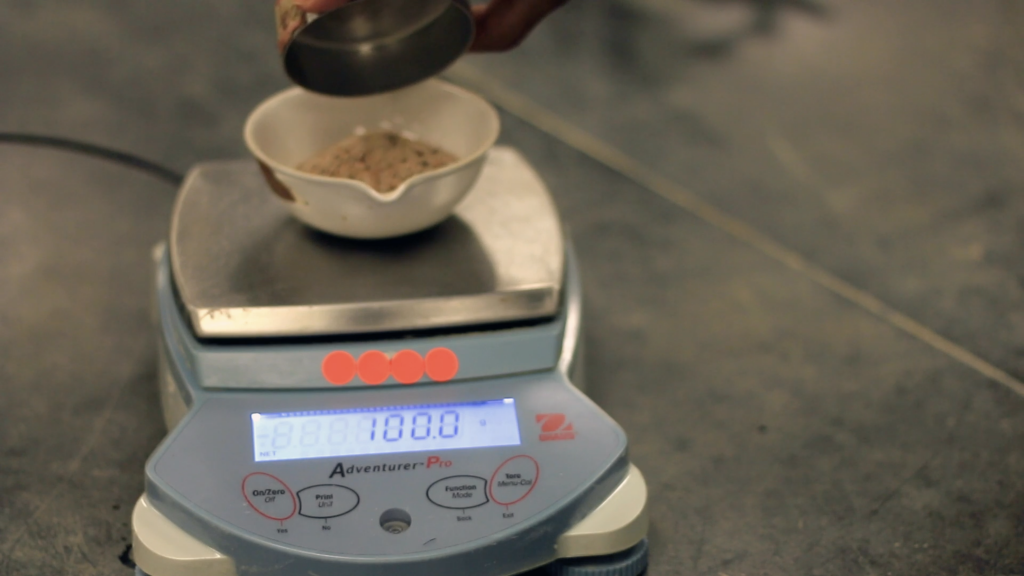 A ceramic bowl is placed over a weighing scale to measure the weight of soil. The scale is showing a value of 100.0 gram.