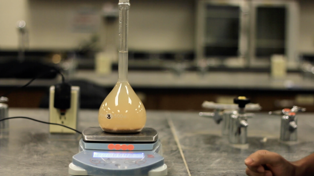 A glass flask filled with soil and water is placed over a weighing scale.