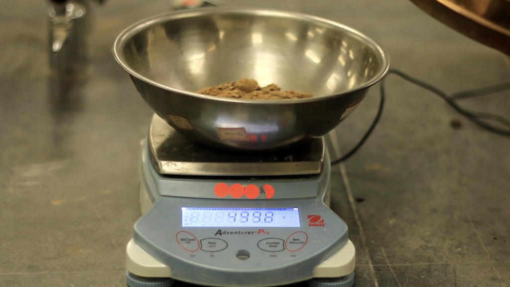 A bowl filled with soil is placed over a weighing scale. Scale shows 499.8 grams.