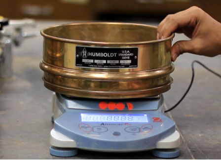 A person is measuring the weight of sieve using a weighing scale