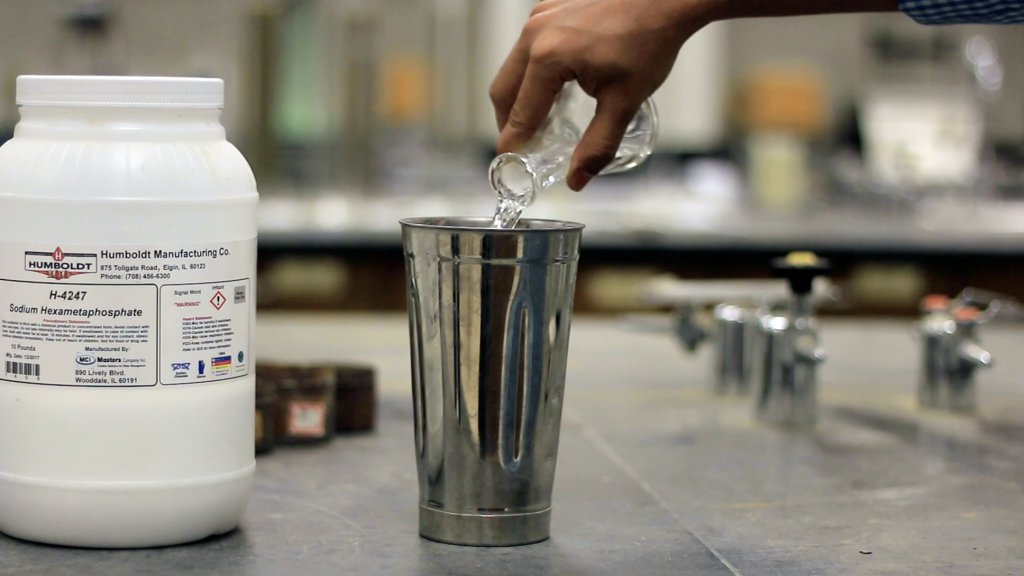 A person is pouring sodium hexametaphosphate solution from a glass flask into a mixing jar. Beside this there is a white container of sodium hexametaphosphate