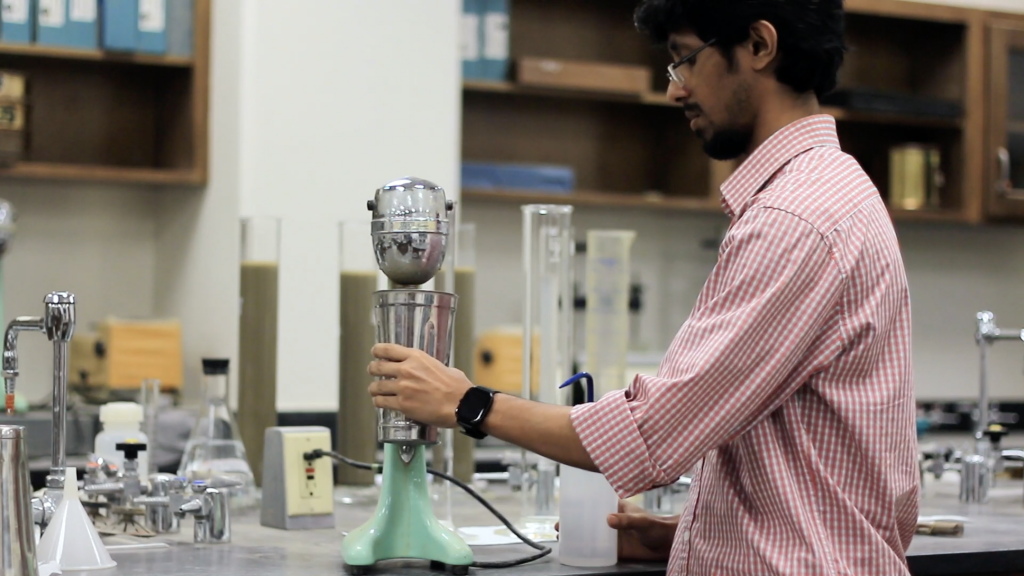 A person a mixing soil slurry. He is holding the mixing jar close to the mixing machine.