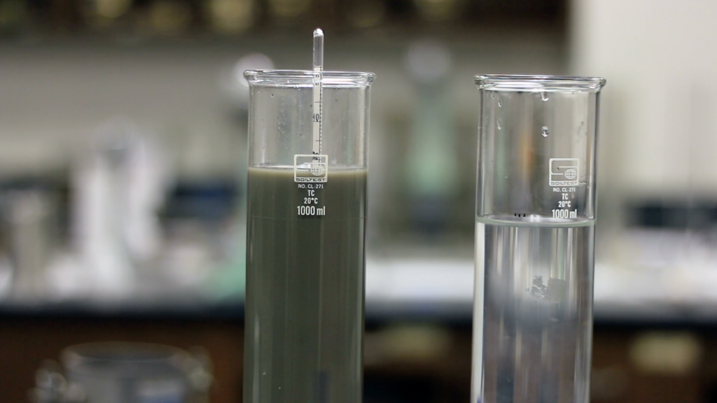 Two glass jar placed side by side. Left glass jar is filled with water and soil mixture which has a scale submerged into it. Right glass jar has water like solution.