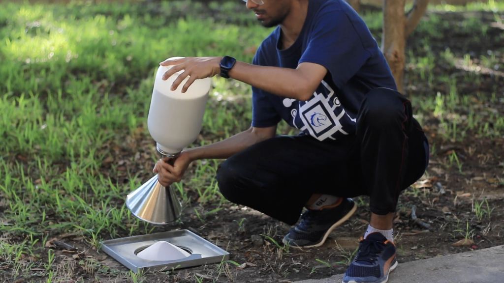 Removing the sand cone apparatus after filling the hole with standard sand