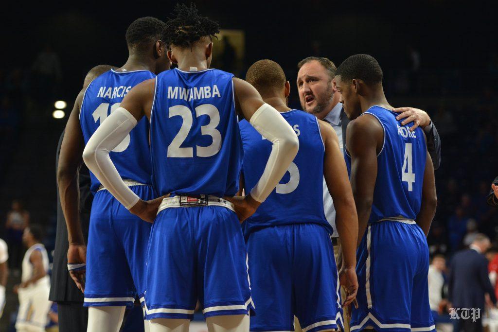 UTA Basketball Players Around Coach Ogden