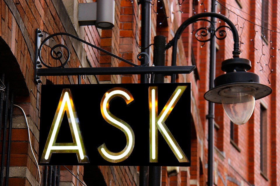 "an illuminated street sign that reads ""ask"""