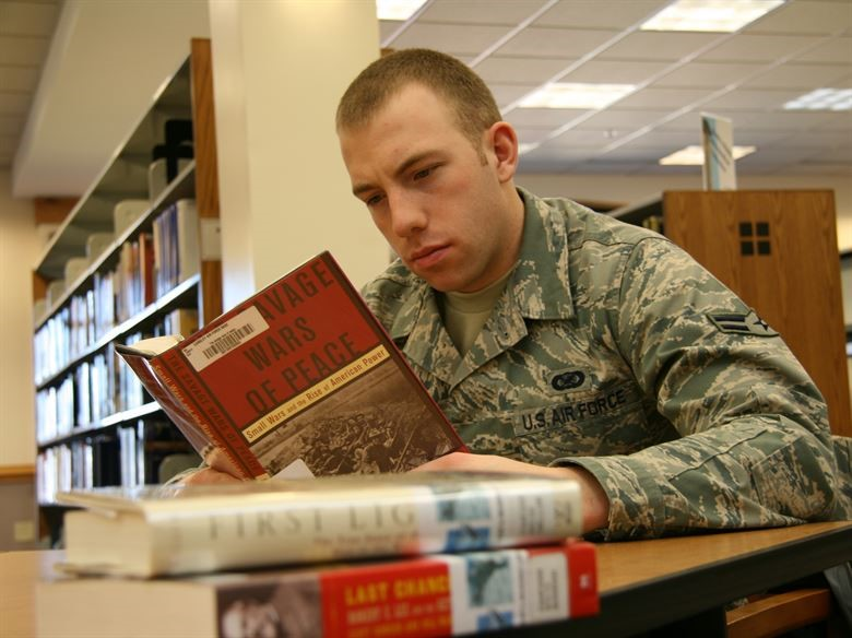 a man in an army uniform reads a book in a library