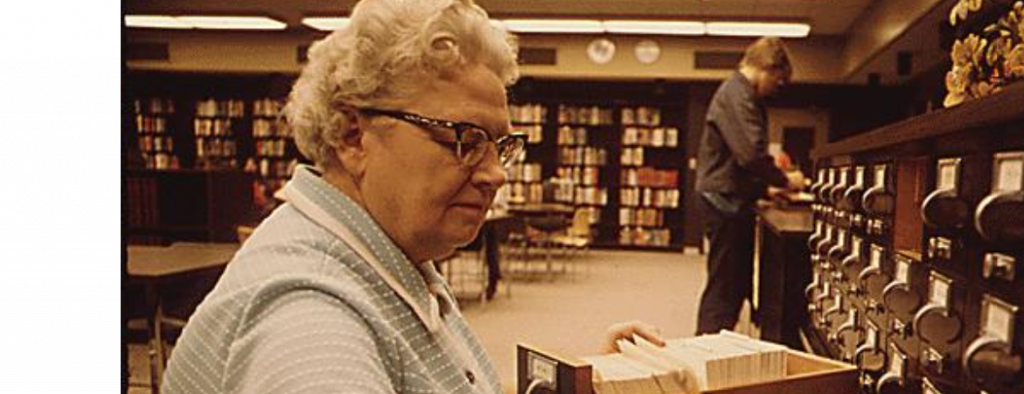 older female librarian sorting a cart catalog